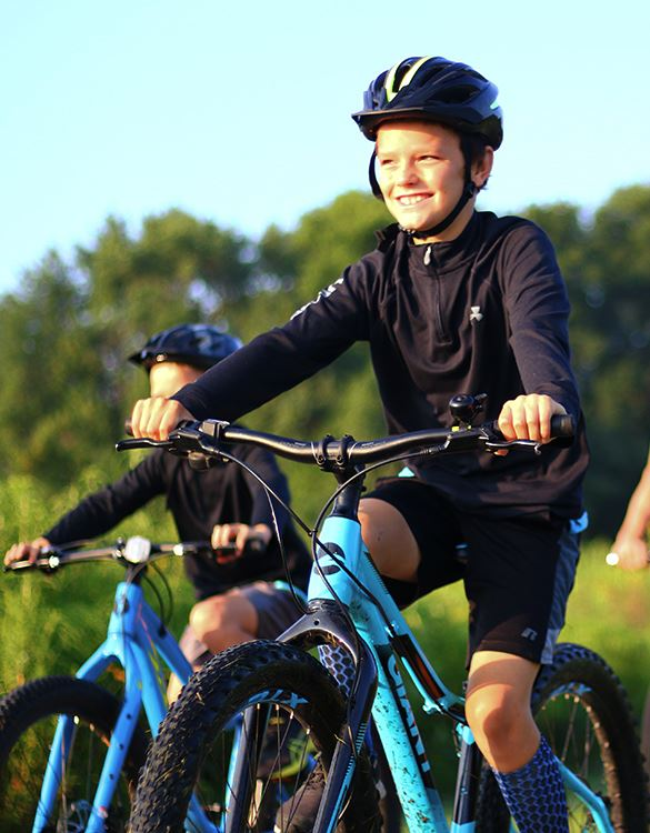 boy wearing a helmet riding his bike