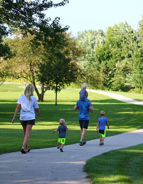 family walking down a path through green grass