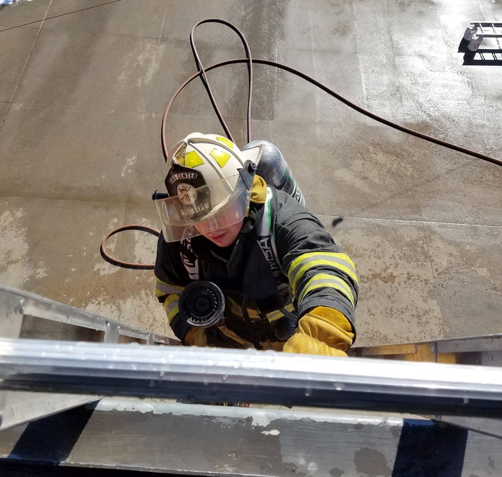 FIrefighter climbs ladder