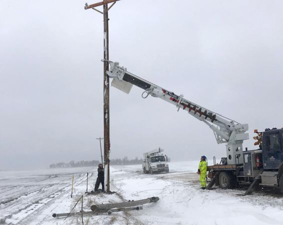 Crew works on electric pole