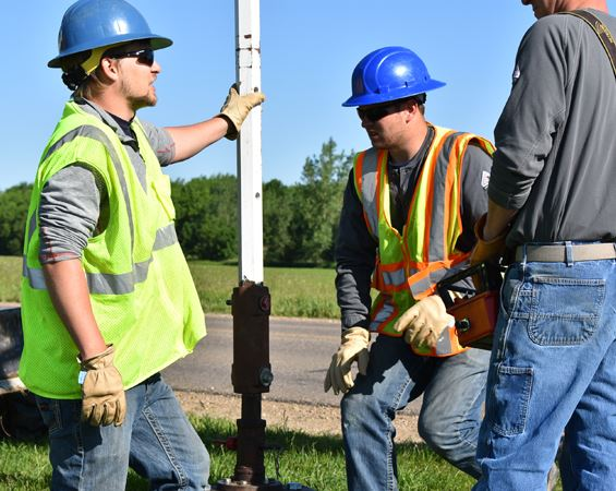 Utility workers in hard hats talk
