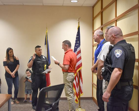 Police officer takes oath of office with others watching