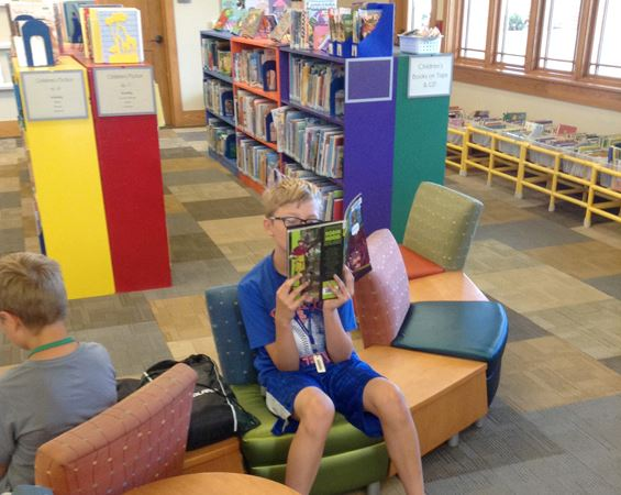 Boy holds book in library
