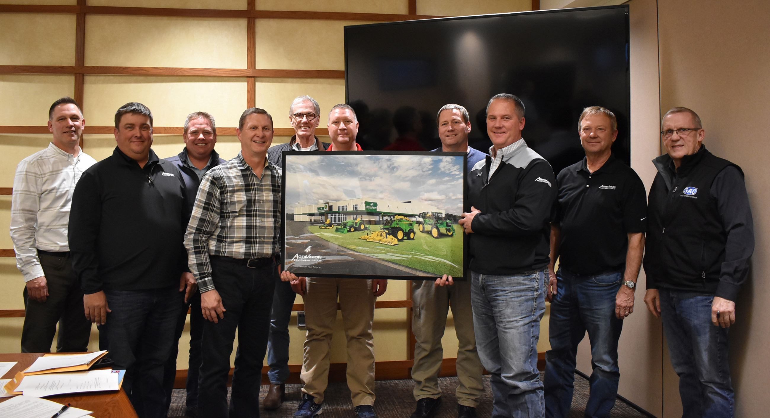 Men hold photo of implement dealership